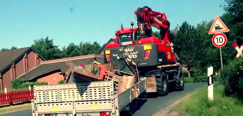 wheel excavator driving on a road with a trailer attached
