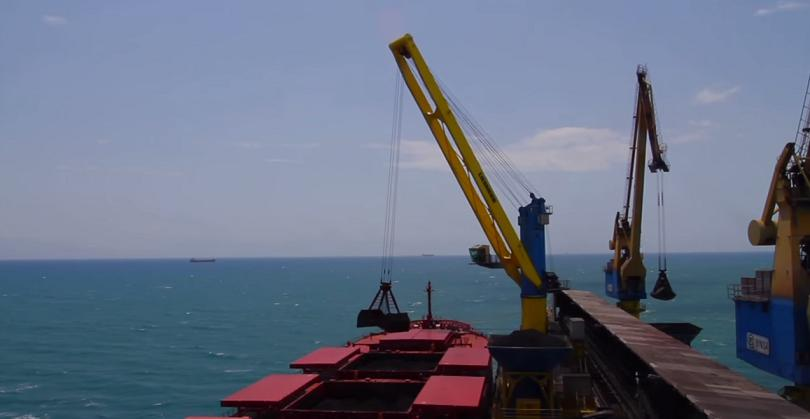 Port crane unloading goods from a boat